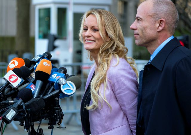 Adult film actress Stormy Daniels speaks to members of the media after a hearing at federal court, Monday, April 16, 2018, in New York, as she is accompanied by her attorney Michael Avenatti.  A judge considering how to handle records seized in an FBI raid on the home and office of Michael Cohen, President Donald Trump