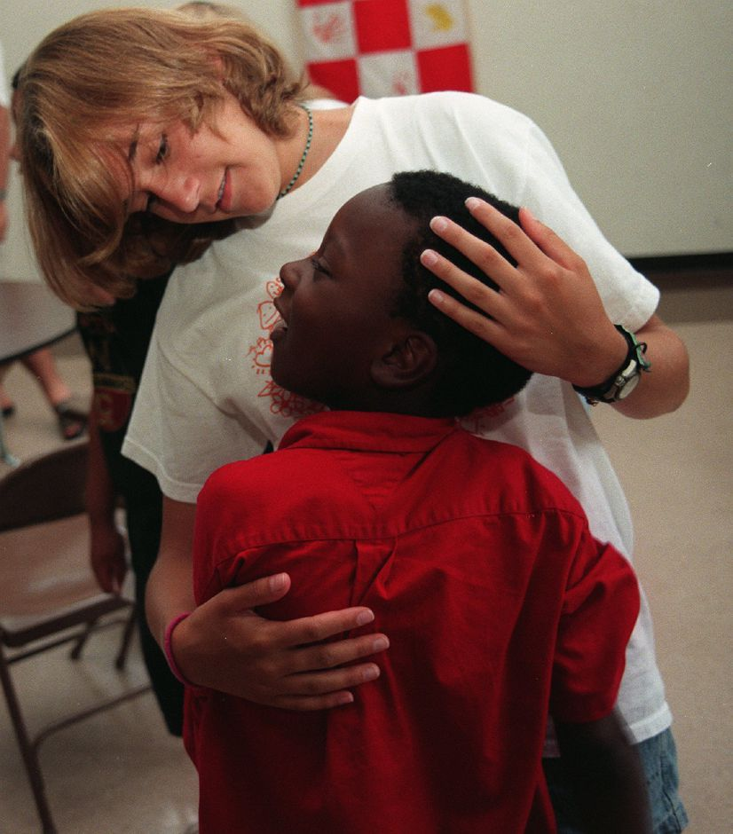 Dujuane McLeod, age 7 from Meriden, recieves a friendly hug after lunch from Bethann Johnson, a professional counselor from New Hampshire at the Emmanuel Lutheran Church summer camp July 19, 1999.