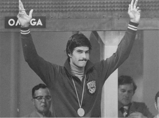 Mark Spitz of Carmichael, Cal., raises his hands acknowledging cheers from spectators after his fourth gold medal in the Summer  Olympic swimming event in Munich August 31, 1972.  He went on to win a fifth gold medal. (AP Photo/stf)