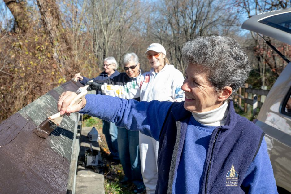 Volunteers restain a wooden guardrail on the Quinnipiac River Linear Trail. The trail