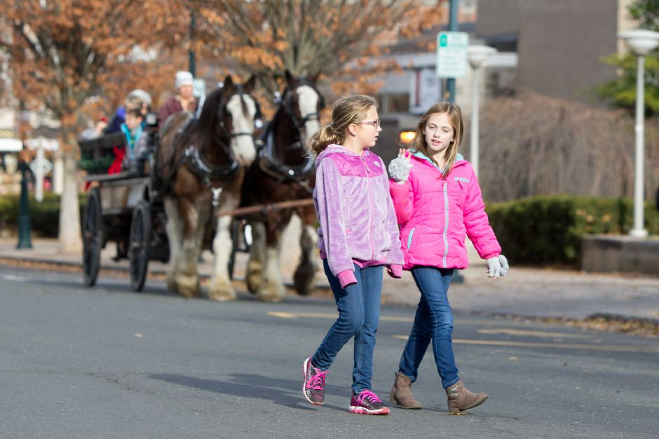 Jordyn Cuff 7 left and Isabelle Champagne 7 cross South Main for the toy train ride Saturday during Season of Celebration at the Town Hall in Wallingford December 2, 2017 | Justin Weekes / For the Record-Journal