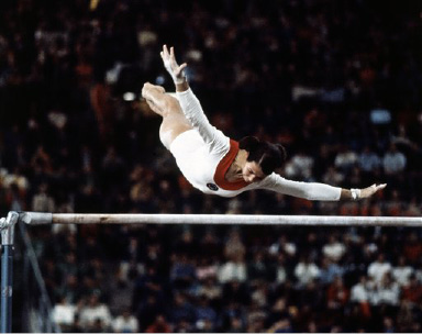 Ludmilla Tourischeva shows how she won her gold medal in performance on the uneven bars in the summer Olympics in Munich on Aug. 30, 1972. She had a winning total of 77,025 points. (AP Photo)