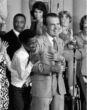Entertainer Sammy Davis Jr. hugs President Richard Nixon from behind as Nixon addresses about 8,000 supporters at a youth rally in Miami, Aug. 22, 1972.  Davis