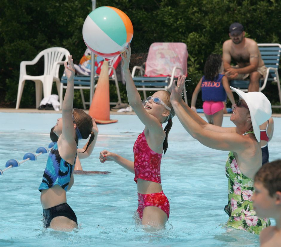 Theresa Viola, 9, left, her sister Grace Viola, 11, and their mother Mary Viola, right, of Wallingford, return the volley of a beach ball while playing in the Wallingford Community Pool Thursday afternoon June 29, 2006. Chris Angileri/Record-Journal.