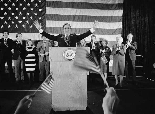 FILE - In this Nov. 7, 1984 file photo, flag-wavers greet Vice President George Bush after he was re-elected to the post of vice president, in Houston, Texas. The vice president
