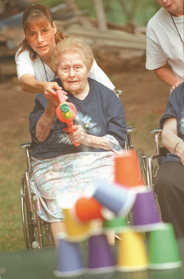 RJ file photo - Laura Hart, a resident at Masonic Geriatric Healthcare Center in Wallingford, takes careful aim at a stack of paper cups with a water gun during the third annual Summer Games at Regency House, Aug. 11, 1998. Glenda Perez, recreation director, helped her.
