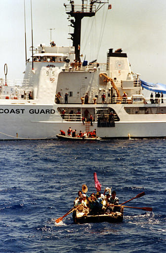 Cuban refugees paddle towaards the USCS Confidence on Aug. 31, 1994. (AP Photo/Eric Gay)