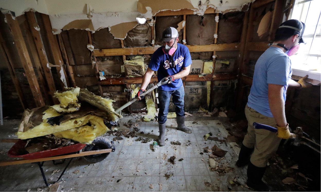 Volunteers Brock Warnick, right, and Colten Roberts remove drywall and insulation from the home of Julia Lluvia which was damaged by floodwaters in the aftermath of Hurricane Harvey Monday, Sept. 4, 2017, in Houston. (AP Photo/David J. Phillip)
