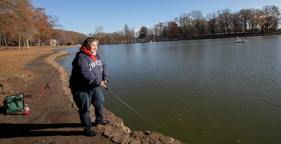 Lisa Giusti, of Meriden, retrieves a line while fishing Mirror Lake at Hubbard Park in Meriden on Friday. Giusti has been fishing the lake for over 40 years with her largest catch being a 5-pound largemouth bass. She also assisted in helping a fellow fisherman reel in a 40-pound carp. Photos by Dave Zajac, Record-Journal