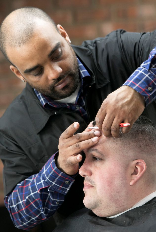 Barber Trey Maestri, owner of Trey's Barbershop, uses a razor while cutting the hair of customer, Bryan Sola, of Southington, at the new business on Center Street in Southington, Wednesday morning, February 21, 2018. Dave Zajac, Record-Journal