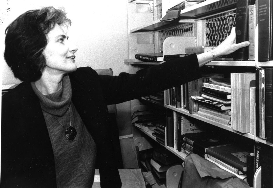 Susan Bullock, library director, with old book about Meriden, Feb. 1986.