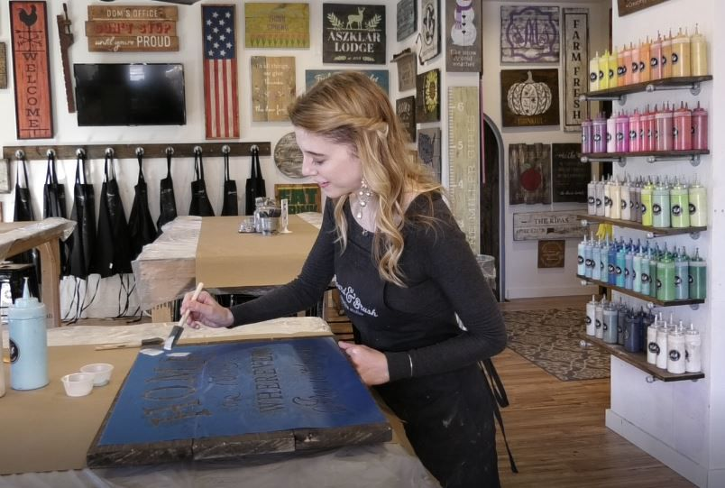 Record-Journal Digital Content Producer Ashley Kus paints a sign at Board & Brush Creative Studio, 61 Center St., Southington. |Ashley Kus, Record-Journal