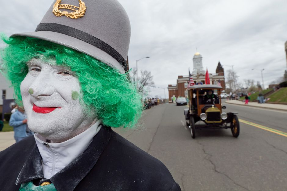 A performer from the Funsters Sphinx Temple of Newington walks down East Main Street in Meriden during the St. Patrick