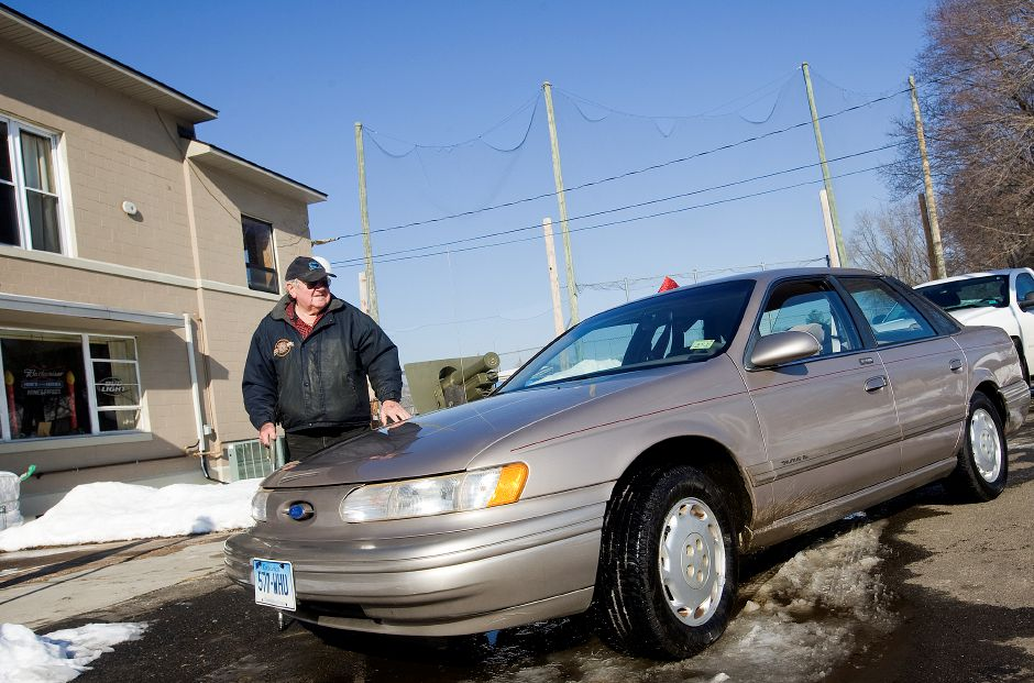 Edward Michalski, of Meriden, a U.S. Army Korean War veteran, stands next to his 1995 Ford Taurus in front of the American Legion Post 45, Thursday, December 19, 2013. The car was donated to him through a team effort at Executive Honda in Wallingford which included Lewis Harper, commander of the Sons of the American Legion Post 45 in Meriden. Harper works as an assistant supervisor in the auto body shop at the dealership and proposed the idea of donating the vehicle after Michalski