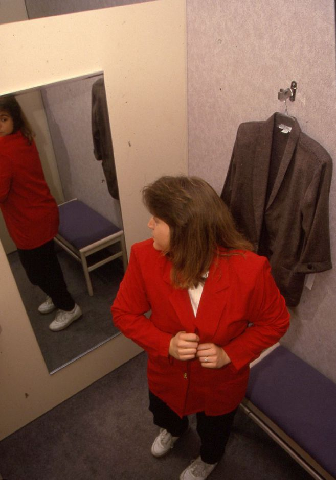 RJ file photo - Debbie Chambers tries on a red jacket in the new dressing rooms at the Sears store in the Meriden Square, Feb. 2, 1994.