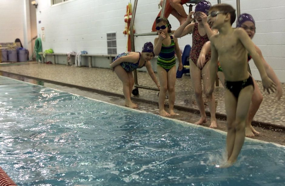 Brandon Rusczek, 8, (far right) is the first to jump into the water during a game of 1-2-3 during the Wallingford YMCA Dolphins Swim Team practice on Monday Feb. 19, 2001. The instructor calls out different numbers and the team members have to jump into the water when the number 3 is called, and get back out quickly. The game helps to build upper body strength. Behind Rusczek from left to right are Gillian Pfeiffer,6; Taylor Duebel,5; Annie Dunleavy,6; and Bridget Casey,6.