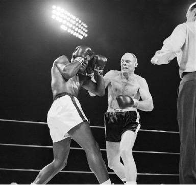 Pete Rademacher, right, hauls off and swings a hefty right as Floyd Patterson covers up in their heavyweight championship boxing match in Seattle August 23, 1957. This type of action was short-lived, however, as Patterson knocked Rademacher the amateur fighting his first pro battle down several times in the fifth round, then knocked him out in the sixth. (AP Photo)