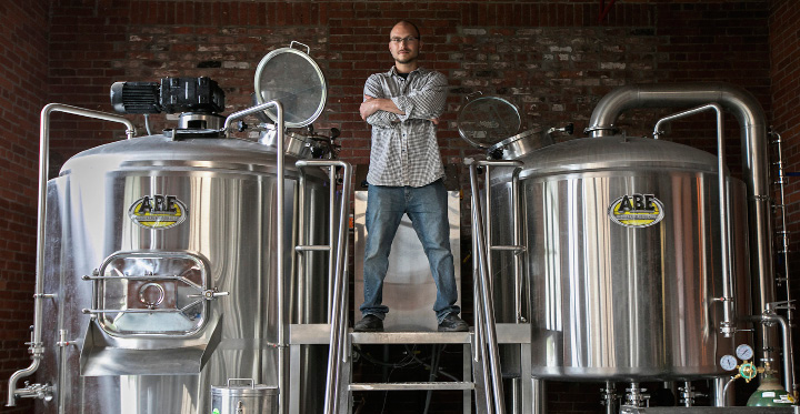 Josh Norris, co-owner of Witchdoctor Brewing Co., stands Wednesday on the brewhouse of the business in Factory Square on Center Street in Southington. | Dave Zajac, Record-Journal