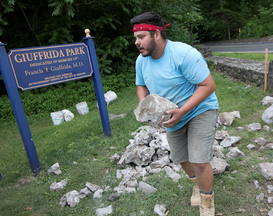Anthony Perez, a worker for Meriden based home improvement contractor Jack Biafore LLC, carries stones from a wall destroyed by a vehicle at the entrance to Giuffrida Park in Meriden, Friday, June 8, 2018. The wall was hit by a vehicle last year. Dave Zajac, Record-Journal