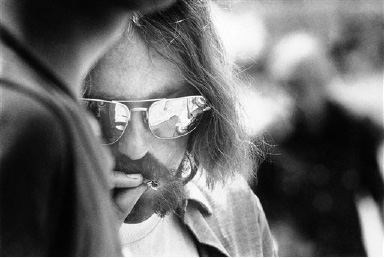 A long-haired hippie puffs on a cigarette during entertainment at the Texas International Pop Festival in Lewisville, Texas on Sept. 1, 1969. The festival in its final round is expected to draw a total attendance of 200,000 people. A first aid tent was kept active treating persons on bad trips from drugs as well as persons suffering from the heat. (AP Photo)