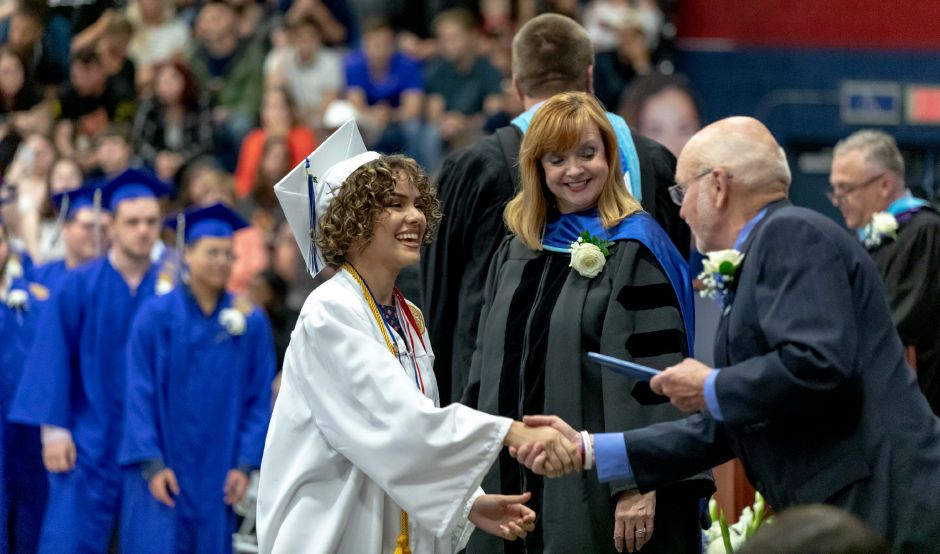 A student shakes hands with Board of Education member Foster White before he hands them their diploma during the Plainville High School graduation ceremony, held in the school