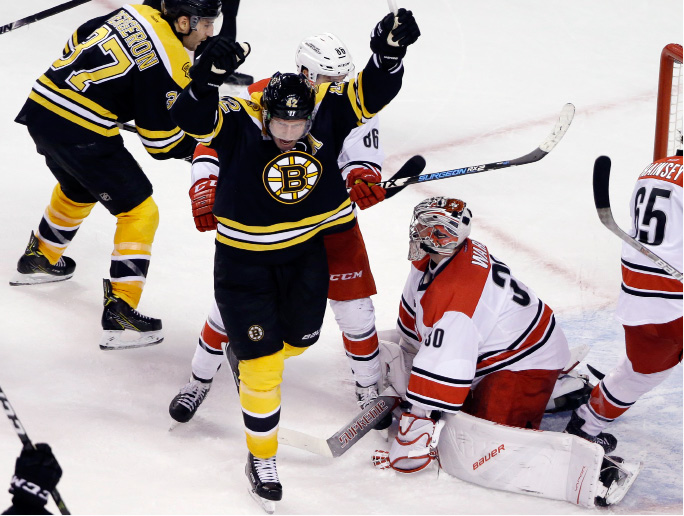 Carolina Hurricanes goalie Cam Ward (30) watches as Boston Bruins right wing David Backes (42) celebrates a goal by teammate Torey Krug to tie the game with seconds to go in the third period of an NHL hockey game, Thursday, Dec. 1, 2016, in Boston. The Bruins won, 2-1, in a shootout. (AP Photo/Elise Amendola)