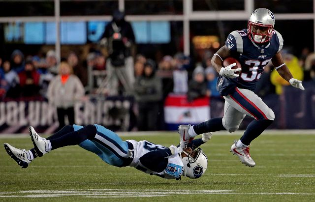 New England Patriots running back Dion Lewis, right, eludes Tennessee Titans cornerback Tye Smith during the first half of an NFL divisional playoff football game, Saturday, Jan. 13, 2018, in Foxborough, Mass. (AP Photo/Steven Senne)