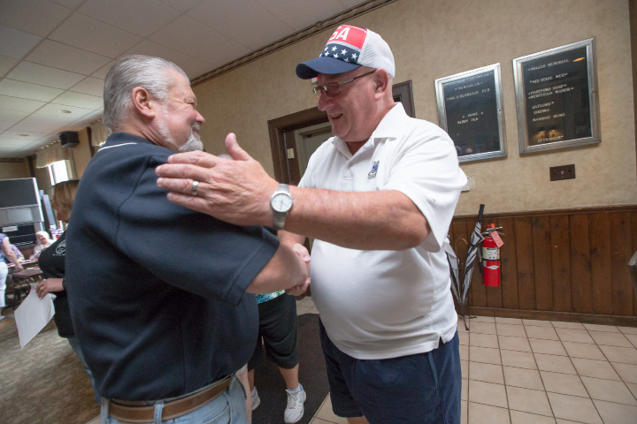 Mike Ruimerman, of Middletown, left, greets fellow father Jim Foley, of Myrtle Beach, South Carolina, Sunday during the Father's Day breakfast.