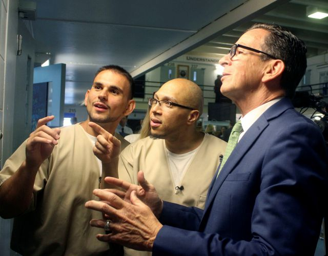 Inmates Festim Shyuqeriu, left, and Isschar Howard, middle, tour Connecticut Gov. Dannel P. Malloy around a unit of the Cheshire Correctional Institution in Cheshire, Conn. on Wednesday May 30, 2018. The TRUE Unit is designed to support the needs of 18 to 25 year old inmates, whose brains are still developing. (AP Photo/Pat Eaton-Robb)