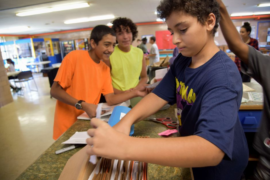Zohir Katim, 13, a Thomas Edison Middle School student, exchanges fake currency with other students at the Meriden Boys & Girls Club on Wednesday, Sept. 19. | Bailey Wright, Record-Journal.