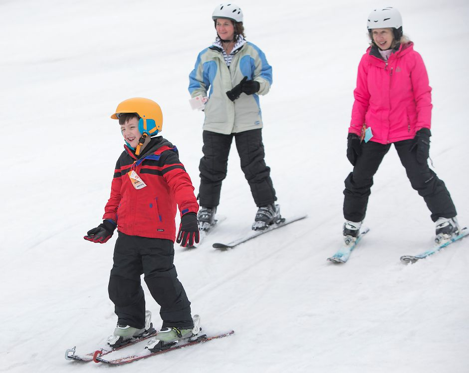 Kellen Blanchette, 6, of Branford, glides down the bunny hill in front of instructors Katie Meriano, of Branford, left, and Marcy Sanders, of Madison, during the Connecticut Children