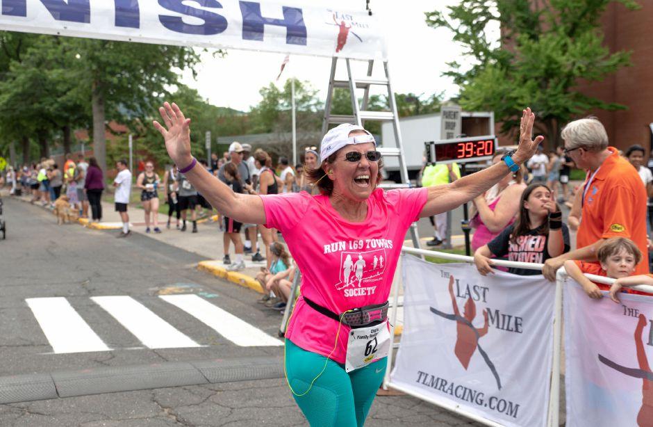 Carolyn Checovetes crosses the finish line of the Chips Family Restaurant Road Race on July 21, 2019. The run started on East Street in front of Plainville High School and ended on Robert Holcomb Way. | Devin Leith-Yessian/Plainville Citizen