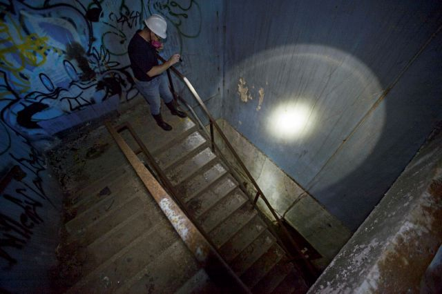 In this Tuesday, Sept. 26, 2017 photo, Derek Boese, the Chief Administrative and Public Information Officer for the Southeast Louisiana Flood Protection Authority-East, uses a flashlight to illuminate the stair well of a Cold War era Civil Defense bunker in New Orleans. In a real nuclear disaster, taking cover in a building bearing a rusted yellow fallout shelter symbol may not be the best option anymore. Experts say the shelters in schools and courthouses are often aging relics from the Cold War that haven't been maintained. And conventional wisdom has changed. (Max Becherer /The Advocate via AP)