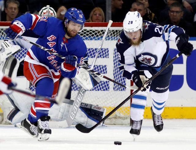 Winnipeg Jets right wing Patrik Laine (29) of Finland keeps the puck from New York Rangers center David Desharnais (51) during the third period of an NHL hockey game in New York, Tuesday, March 6, 2018. (AP Photo/Kathy Willens)
