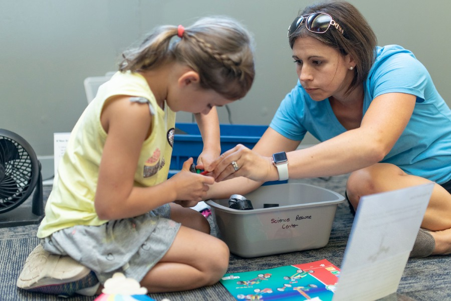 Wallingford-residnt Erica Ballas helps Evie Ballas, 6, construct a sail-powered lego car. Math games and engineering tasks were laid out in the Oakdale Theater on August 19, 2019 as part of the Wallingford School
