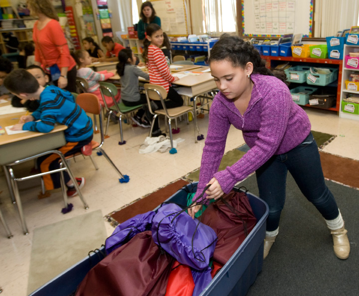 Cindy Sanchez, 8, adds another backpack filled with school supplies to a tote at Roger Sherman Elementary School in Meriden, Tuesday, December 13, 2016. Students recently made and sold hundreds of school spirit bracelets to purchase backpacks and school supplies for less-fortunate city children. | Dave Zajac, Record-Journal