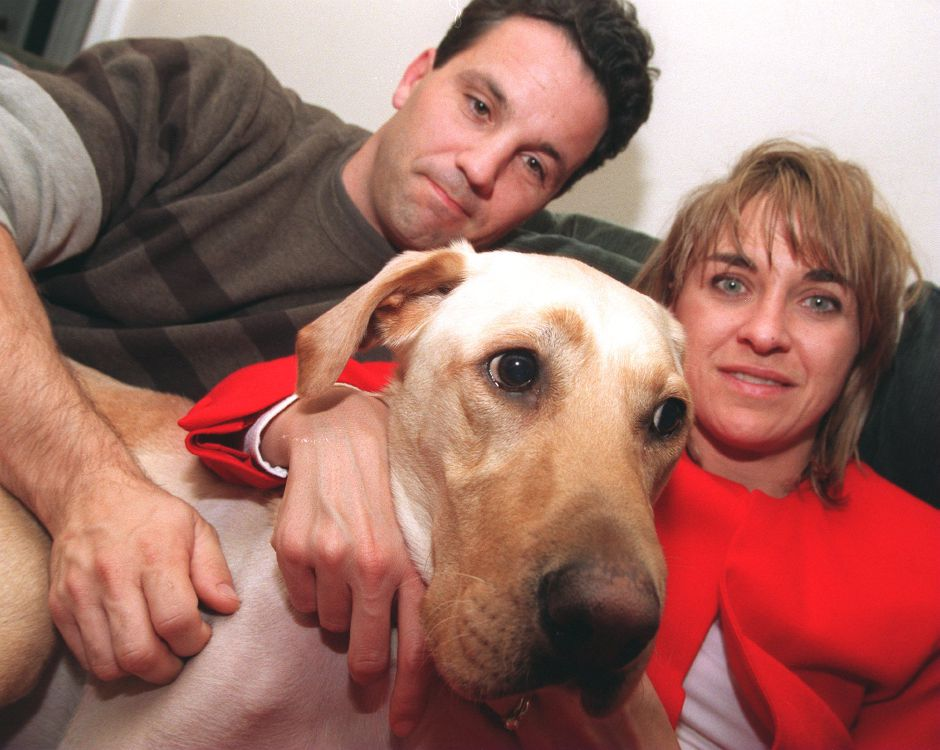 RJ file photo - Scott and Mary Gina Ratchford hunker down with Jake, their yellow Labrador retriever, in their Southington home, Dec. 1998. Jake is making a miraculous recovery after falling about 75 feet last month and the couple want to thank the hikers who helped rescue him.