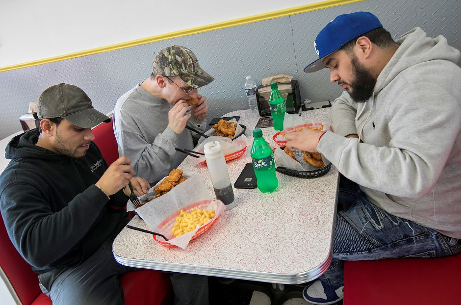 Left to right, Manuel Mateo, of Meriden, Jake Sizemore, of Wallingford and Walter Martinez, of Meriden, dig into chicken entrees during lunch at the new Cheek