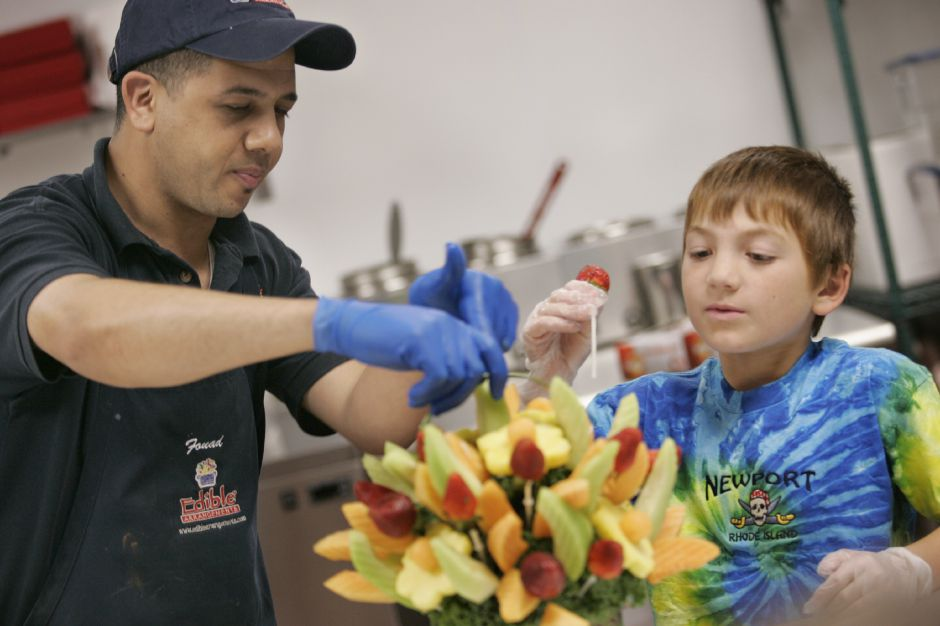 Fouad(cq) Elgoute (cq), left, helps Stevens school student Domonic (cq) Perrotti, 9, of Wallingford create a fruit bouquet during a field trip at Edible Arrangements in Wallingford Tuesday October 2, 2007. Elgoute (cq) is production manager at the business located at 95 Barnes Rd. (dave zajac photo)