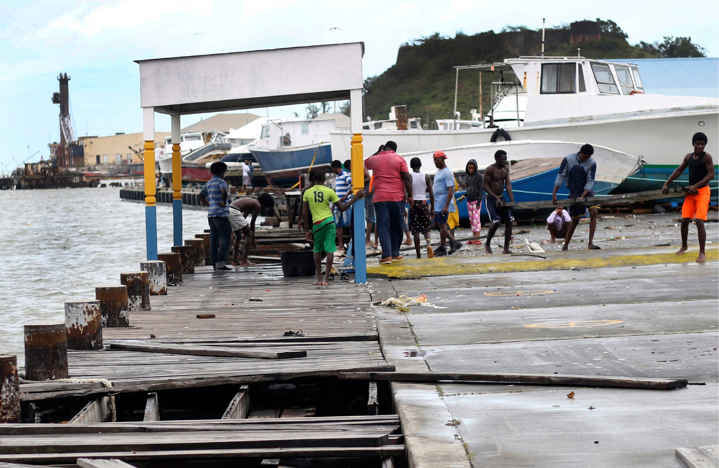 People recover broken parts of the dock after the passing of Hurricane Irma, in St. John