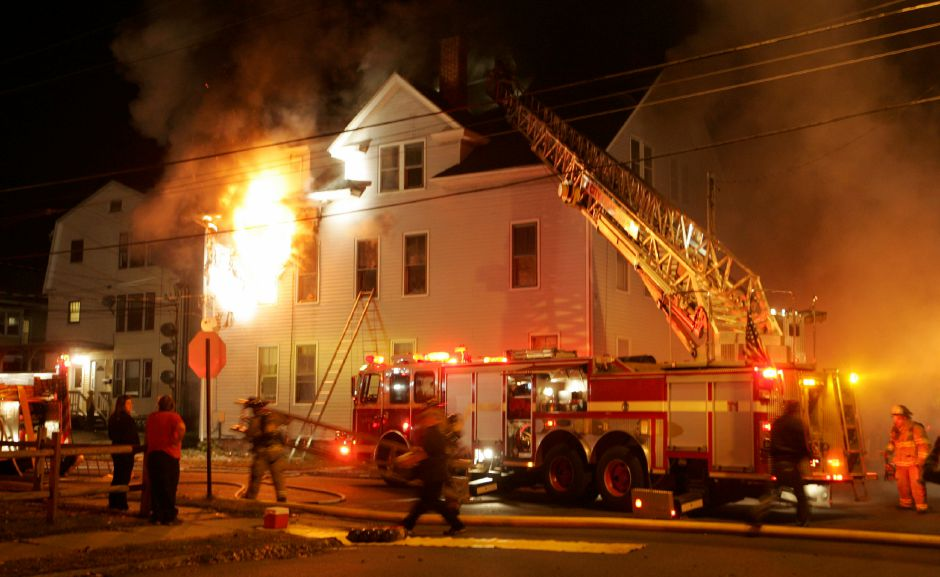 Flames shoot out the second floor of a three story apartment house as Meriden firefighters work to contain a blaze at 124 Sherman Ave. November 1, 2009. (dave zajac photo)