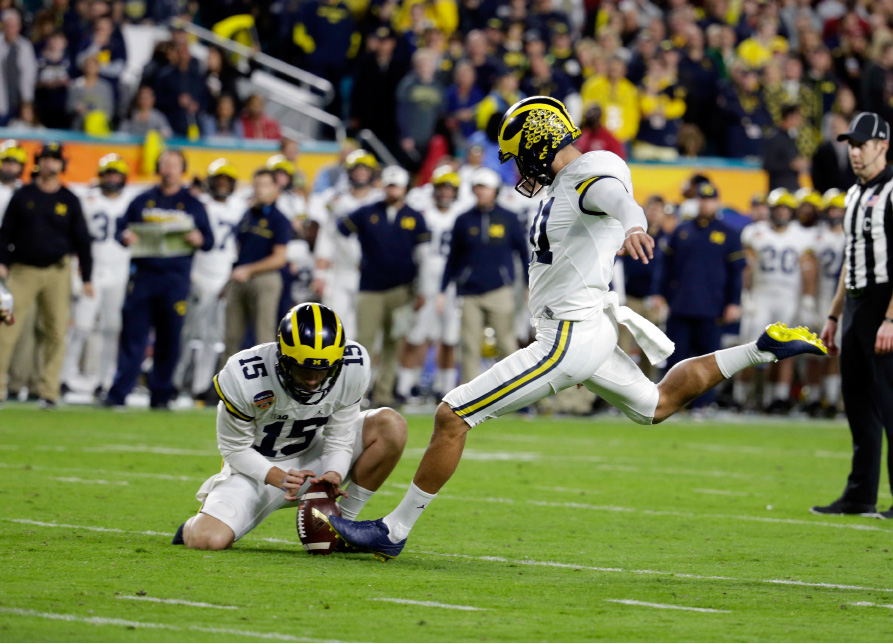 Michigan place kicker Kenny Allen (91) kicks a field goal as quarterback Garrett Moores (15) holds, during the first half of the Orange Bowl NCAA college football game against Florida State, Friday, Dec. 30, 2016, in Miami Gardens, Fla. (AP Photo/Lynne Sladky)