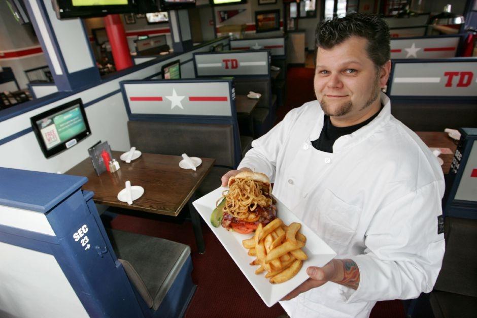 Executive Chef Bill Nemecek holds a Big BBQ burger, one of several signature gourmet burgers now available on an all new menu at TD Homers located at 461 Queen Street in Southington. (Dave Zajac/Record-Journal)