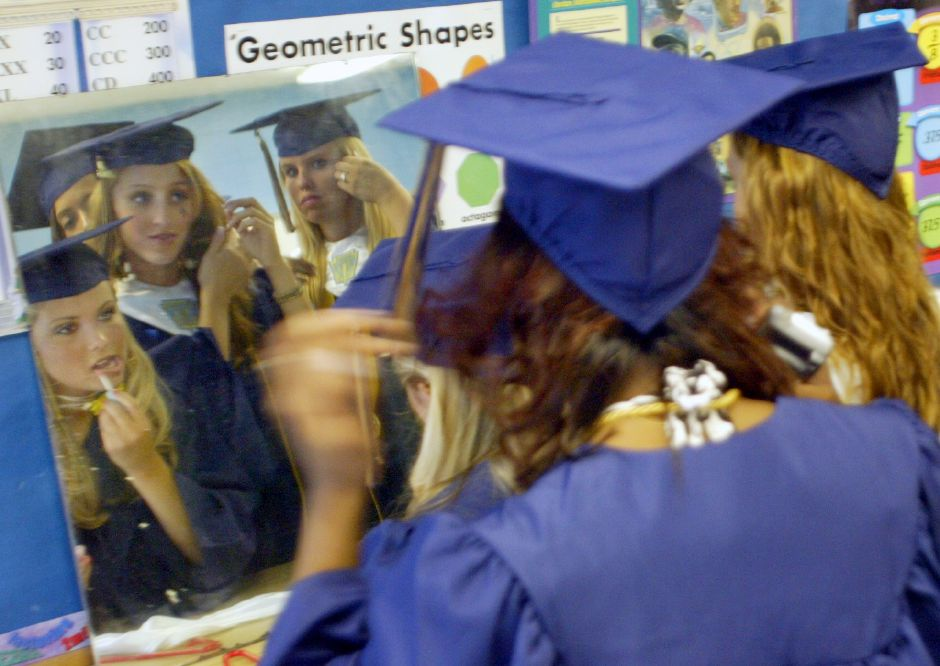 At far left Christiana(cq) Schlett, 17, applies some last minute lipstick while sharing a mirror in a classroom with fellow graduates before commencement ceremonies at Platt High School June 20, 2006. (dave zajac photo)