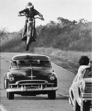 "Stunt cycle rider John Mulber leaps over a moving car during a chase scene of the movie production of ""Stingray"" which is being shot in the St. Louis area, Aug. 22, 1977. The production, a spoof on other cops and robbers stunt filled chases, is due for release in early 1978. The jump is being filmed from the car in right foreground. (AP Photo)"