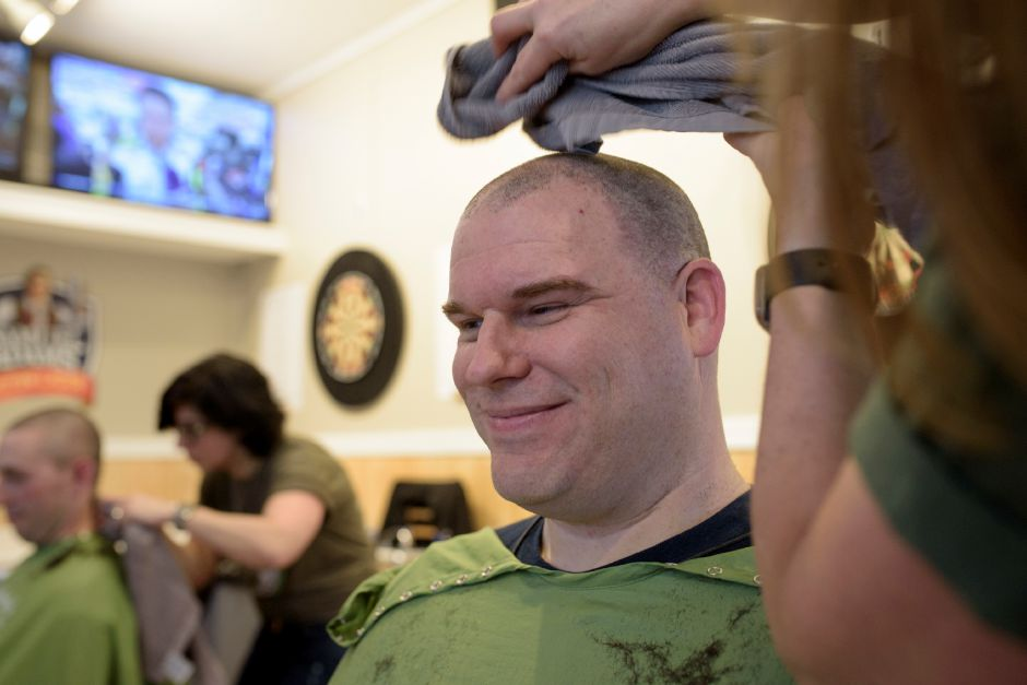 Karen Brown of Headstrong Salon in Wethersfield cleans off Dan Spetland of North Haven Fire after shaving his head during the St. Baldrick