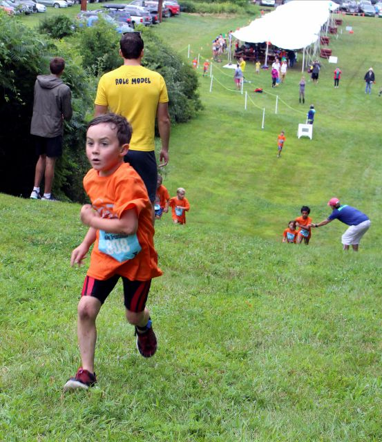 FILE - In this Aug. 5, 2017 file photo, six-year-old Henry Gerl of Clinton, Conn., runs in the fourth annual Race4Chase kids triathlon finale in Southington, Conn. The program, founded by the family of Chase Kowalski, who was killed in the December, 2012 Sandy Hook shootings, has grown to more than 20 sites in three states. (AP Photo/Pat Eaton-Robb, File)