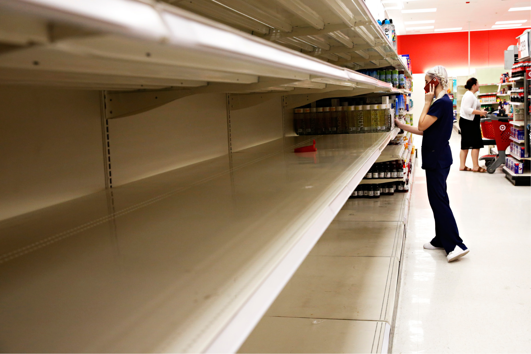"Kailey Coventry walks past empty shelves of water at Target in Gainesville, Fla., on Wednesday, Sept. 5, 2017. ""Hurricanes are always super last minute but I just want to make sure I"