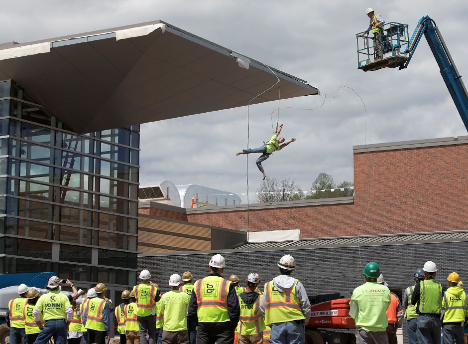 A dummy is pulled off a roof as part of a safety demonstration by O&G Industries at Platt High School in Meriden, Wednesday, May 3, 2017. Steve Baranello, project superintendent, top right, headed the demonstration, which consisted of pulling a life-sized, partially-harnessed dummy off a roof, to show the dangers of construction workers not taking proper safety precautions. | Dave Zajac, Record-Journal