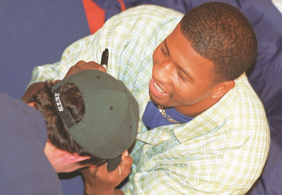 RJ file photo - Larry Whigham of the New England Patriots smiles as he signs an autograph on the brim of a New York Jets cap at the Meriden Square mall Dec. 21, 1998. Whigham, who becomes a free agent next season, hopes to be with the Patriots when they move to Harford.